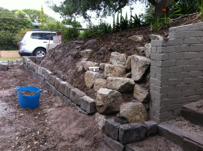 The new driveway edge with recycled bluestone and relaid granite rock wall